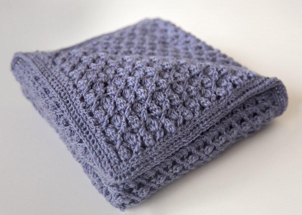 The diagonal cluster stitch in combination with this DK weight yarn helps to create a delicate lace crochet fabric that's perfect for an heirloom baby blanket.