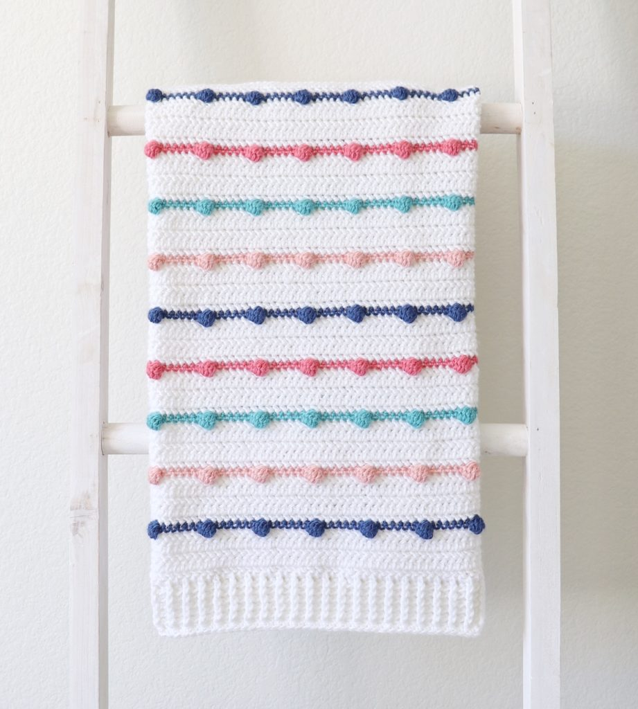 Do you have some leftover yarn lying around in your yarn stash? Pull them out of your closet and put them together in this beautiful and easy baby blanket pattern.