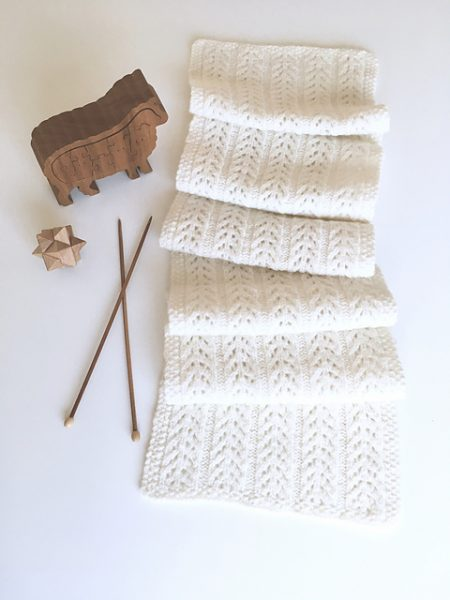 A simple lace knit scarf with five panels of branching pattern repeats and a moss stitch edging border.